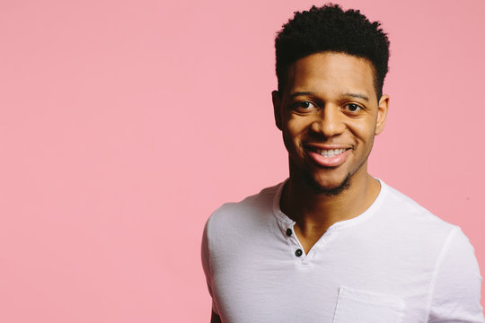 Portrait of a cool African American guy in white shirt looking at camera with a big smile, on pink background