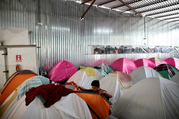 Orlin, 19, a migrant from Honduras, fixes his camping tent inside the Juventud 2000 shelter in Tijuana