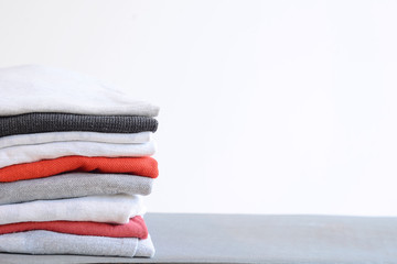 Stack of colorful folded shirts on gray table
