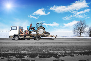 Tow truck with old tractor on the winter countryside road against blue sky with sun