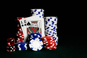 Stacks of poker chips on a gambling table with an ace and king representing a Blackjack win playing the game 21