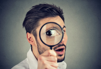 Curious man looking through a magnifying glass