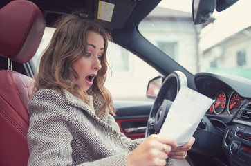 Shocked woman in car reading insurance paper