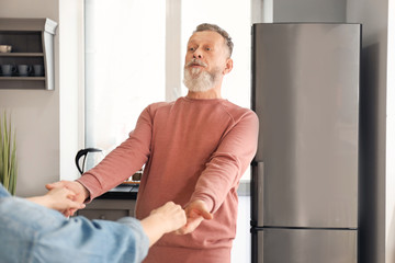 Happy mature couple dancing in kitchen