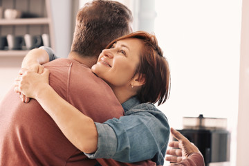 Happy mature couple hugging at home