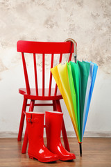 Stylish rainbow umbrella, rubber boots and chair indoors