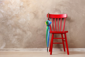 Stylish rainbow umbrella and chair near brown wall
