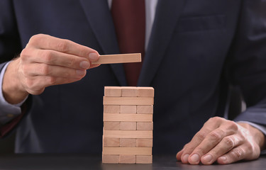 Man building tower from wooden blocks on table, closeup