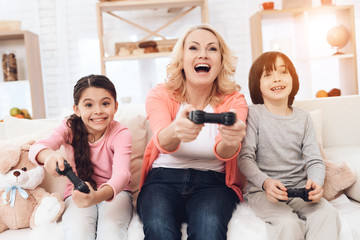 Joyful grandmother with cheerful grandchildren playing on game console sitting on couch.