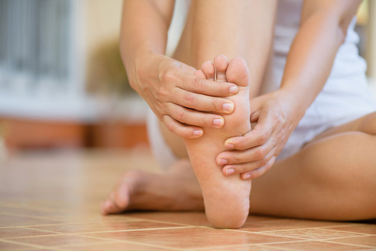 Closeup young woman feeling pain in her foot at home. Healthcare and medical concept.