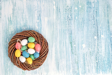 Easter wreath with colorful Easter eggs on blue background. Top view, copy space. Easter decoration