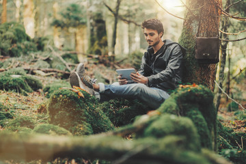 Man using a tablet in the forest