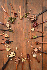 Assortment of beans and lentils in wooden spoon on teak wood background