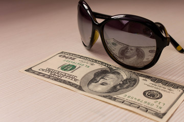 $ 100 is reflected in the glasses . On a beige background