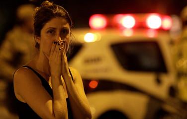 A woman reacts as she observes the crime scene where Rio de Janeiro city councilor Marielle Franco was shot dead in Rio de Janeiro