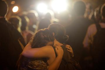 Women react next to the crime scene where Rio de Janeiro city councilor Marielle Franco was shot dead in Rio de Janeiro,