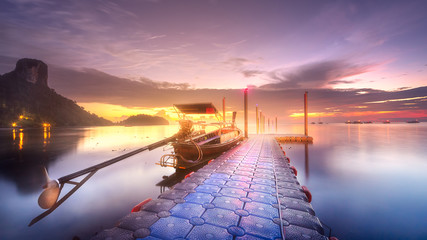 Tropical tranquil shore and pier in rays of dawn