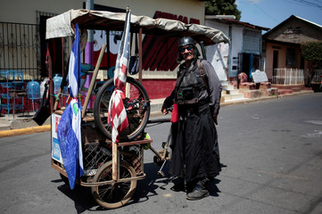 A man dressed as a character from Star Wars poses for a photo as he sells newspapers in Masaya