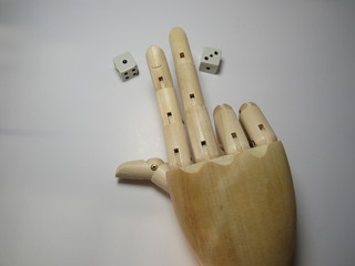 wooden hand playing with dice