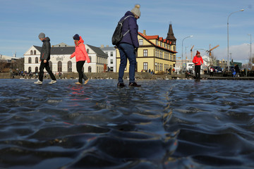 Tourists walk across water frozen into a ripple pattern on a pond in Reykjavik, Iceland