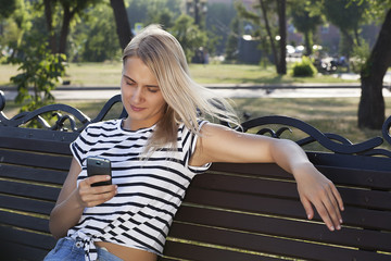 young beautiful blonde girl talking on mobile phone and smiling, talking on phone in park