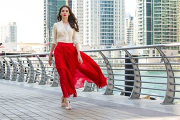 Attractive, Slim, Beautiful And Brunette Girl Wearing White Shirt And Maxi Long Red Silk Fabric Skirt Fly And Wave In The Wind Walking Alongside Dubai Marina Middle East Fashion Concept
