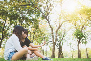 Two beautiful happy young asian women friends having fun together at park and taking a selfie. Happy hipster young asian girls smiling and looking at smartphone. Lifestyle and friendship concepts.