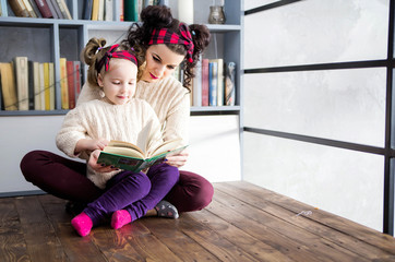 mother and daughter are sitting on the floor and reading