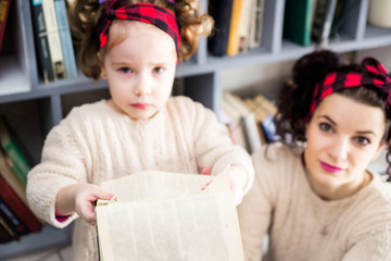 A little girl and her mom are upset because of a torn book