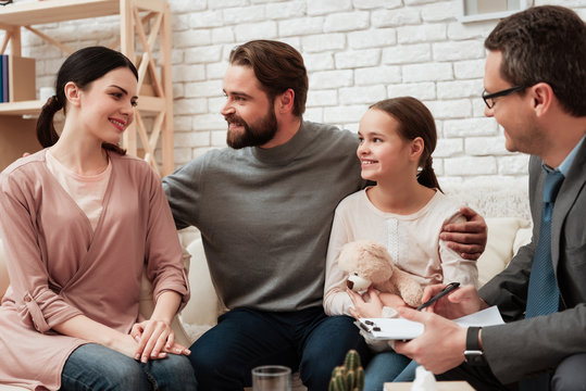 Happy family of three talking with psychologist. Family psychotherapy concept.