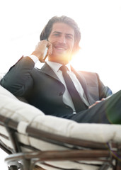 business man talking on a smartphone while sitting in a comforta
