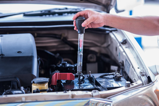 Using the battery hydrometer measuring gravity of battery distilled water, maintenance cars battery concept.