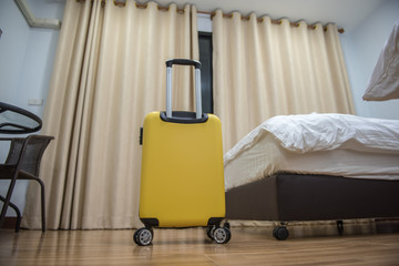 Yellow travel suitcase in the bedroom and window curtain background - relaxing time, holidays, weekend and traveling concept.