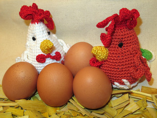 Knitted hens with fresh eggs. Easter chickens