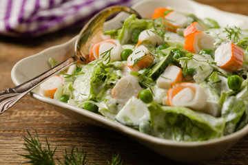 Crab sticks salad with peas, cucumber and mayonnaise.