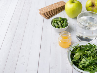 Healthy diet food on the table Arugula Green Beans Apple Water Honey Cracker