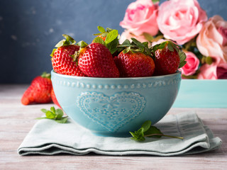 Fresh spring strawberries in blue bowl with heart and pink roses in the background
