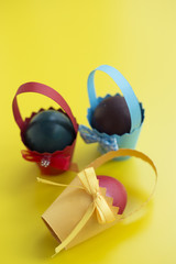 Colorful eastern eggs warped in paper cups on yellow background. Selective focus