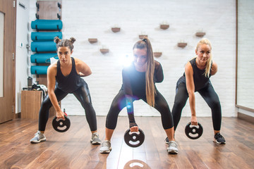 Group of three young sporty women exercising with weights in gym.