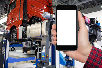 Hand with phone on a background of truck on a lift in a car service