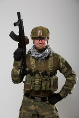 Portrait of soldier in safety glasses with gun in his hand
