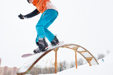 Image of sportive man skiing on snowboard from springboard