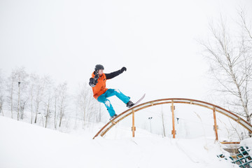 Picture of young sportive man skiing on snowboard with springboard against background of trees