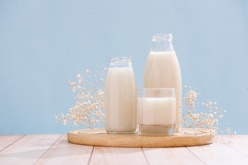 Dairy products. Bottle with milk and glass of milk on wooden table