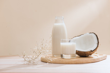 Coconut milk in bottle and glass on table with copy space