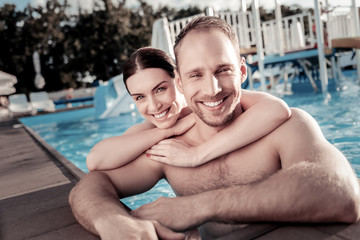 Time to relax. Loving young woman and man embracing and looking into the camera with cheerful smiles on their faces while saying in a swimming pool.