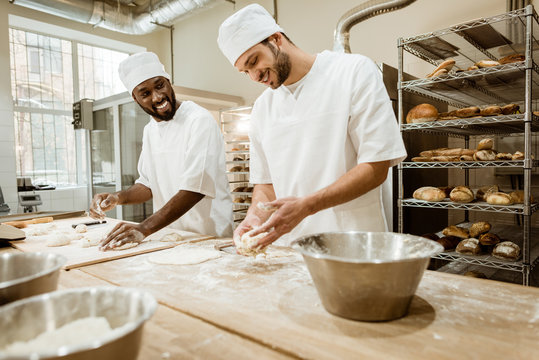 happy bakers kneading dough together at baking manufacture and talking