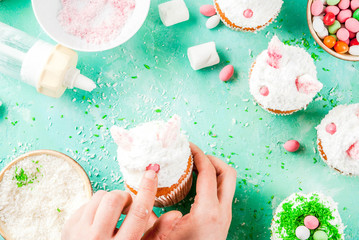 Making easter cupcakes, person decorate cakes with bunny ears and candy eggs, copy space frame top view, girl's hands in picture