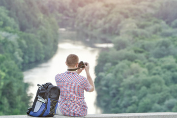 Man takes pictures from a hill. Forest and river below