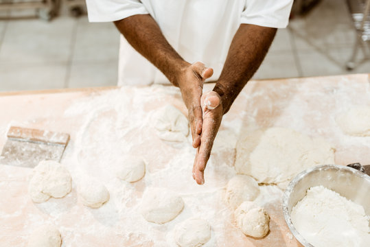 cropped shot of african american baker preparing dough balls for pastry and covering hands in flour